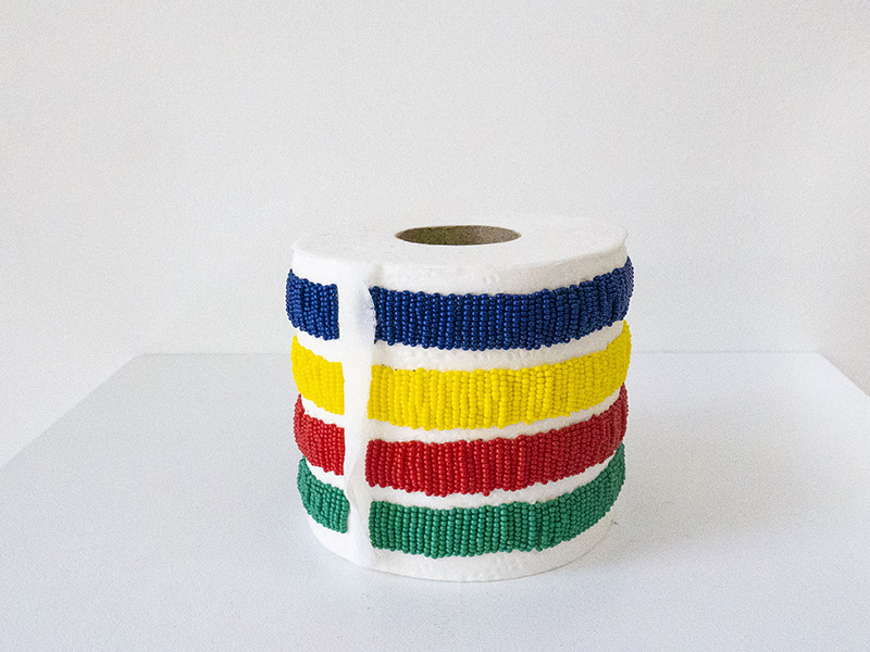 A toilet paper roll beaded in blue, yellow, red and green stripes