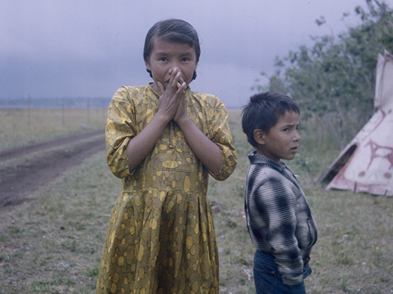 Young girl and boy standing on grass, between a teepee and a dirt road