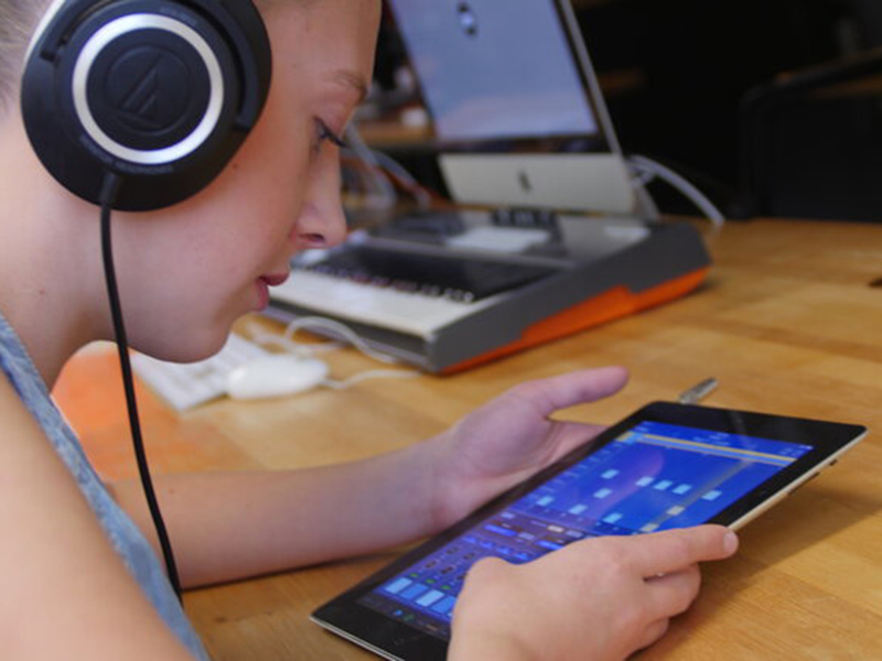 A kid with a tablet and headphones