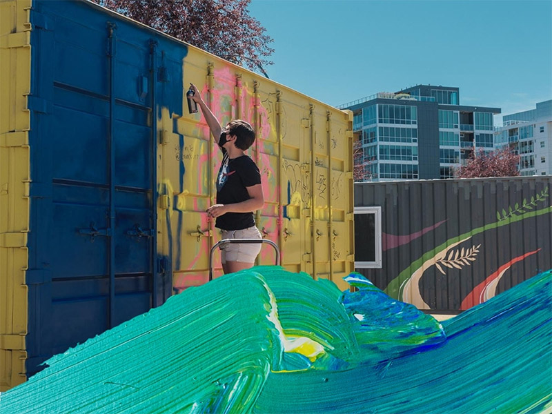 A person works on a mural as part of the Youth Mural Project at containR