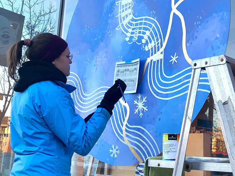 Jessica Semenoff Art painting her piece for the 2021 Northern Reflections Window Exhibition