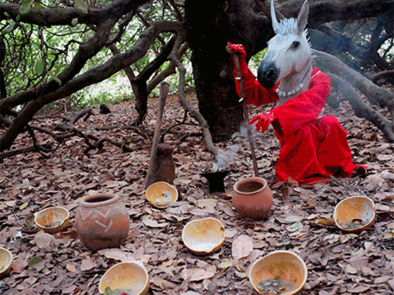 A piece in Notes for Tomorrow of a person wearing a horse mask under a tree with pottery scattered on the ground