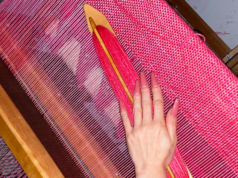 A photo of Molly JF Caldwell weaving on a loom
