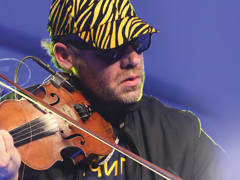 A promo photo of Ashley MacIsaac on stage