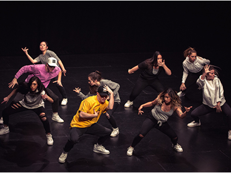 Image of eight dancers on stage mid-choreography
